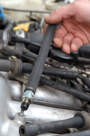Modern car gasoline engine servicing, workers hands and spark plug,selective focus photo