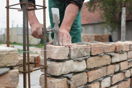 Mason hands making wall with mortar and bricks Stock Photo