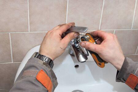 allen key: Plumber fixing water tap in a bathroom using allen key