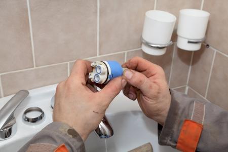 Plumber fixing water tap ceramic cartridge valve in a bathroom