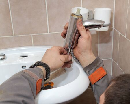 Plumber fixing water tap in a bathroom photo