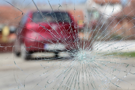 collision: Broken windshield with red car in background