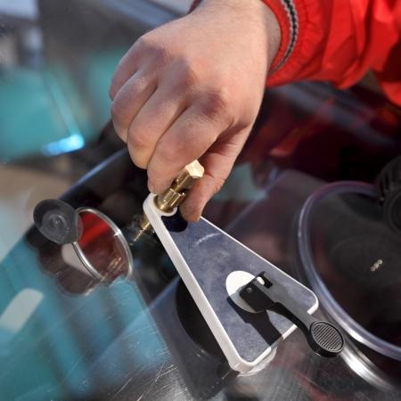 Mechanic using repairing equipment to fix damaged windshield Imagens
