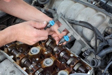 fuel: Car mechanic fixing fuel injector at  two camshaft gasoline engine