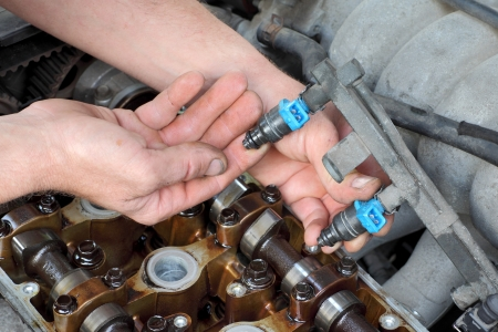 Car mechanic fixing fuel injector at  two camshaft gasoline engine photo