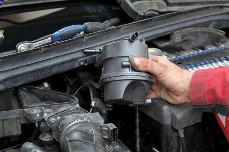 Car mechanic replacing fuel filter at modern diesel engine