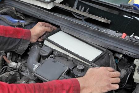 papel filtro: Mantenimiento del coche, en sustituci�n del filtro de aire de papel de motor moderno Foto de archivo