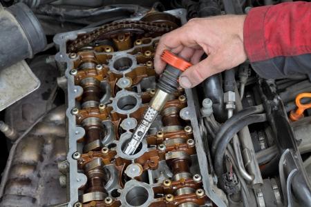 bobina: Mecánico de coche reemplazar la bobina de encendido en el motor de gasolina Foto de archivo