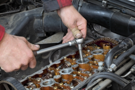 handtool: Mechanic fixing spark plug to open car engine with ratchet, visible camshafts,  pulley, belt, timing chain