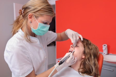 Female dentist doctor cleaning and polishing  young patient tooth  Stock Photo