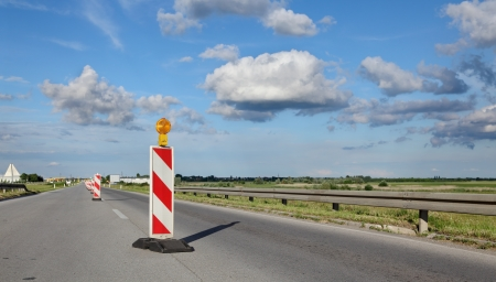 redirection: Roadworks, road sign in a highway on reconstruction with blue sky and clouds Stock Photo