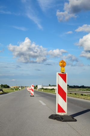 roadwork: Roadworks, road sign in a highway on reconstruction with blue sky and clouds Stock Photo