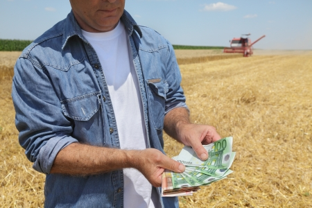 Farmer holding Euro banknote with combine harvester in background