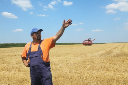 Farmer in wheat field with combine harvester in background photo