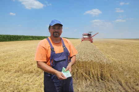 cash crop: Farmer holding Euro banknote with combine harvester in background