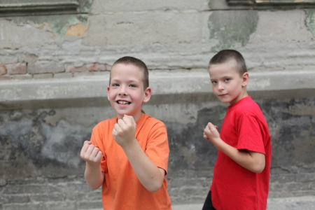 boy boxing: Two young playful Caucasian boy boxing at street
