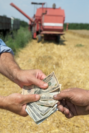 Farmer and buyer hands holding dollar banknote in wheat field with combine in background photo