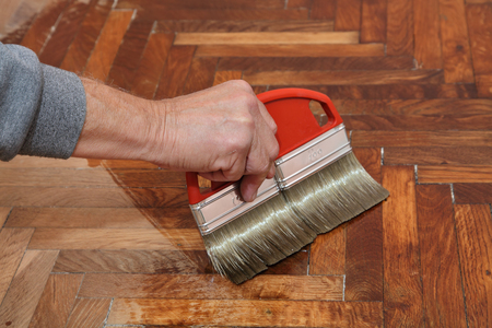 treated board: Varnishing of oak parquet floor, workers hand and brush