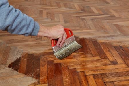 オーク材の寄木細工の床、労働者の手とブラシのニスを塗る