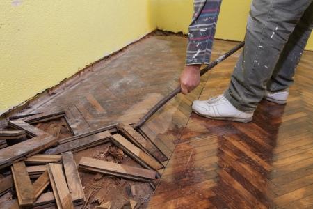 Worker demolishing oak parquet with crowbar tool