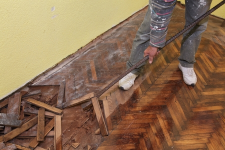 Worker demolishing oak parquet with crowbar tool