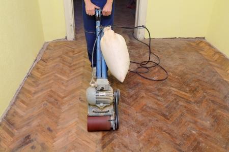 Trabajador pulido viejo piso de parquet con máquina de pulir