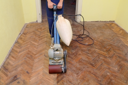 sanding: Worker polishing old parquet floor with grinding machine Stock Photo