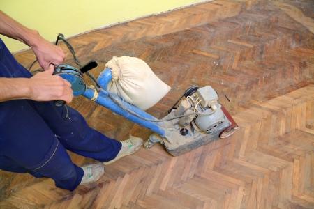 Werknemer polijsten oude parketvloer met slijpmachine Stockfoto