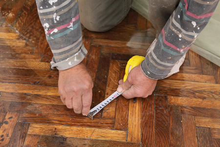 Worker measuring and marking parquet floor for cutting photo