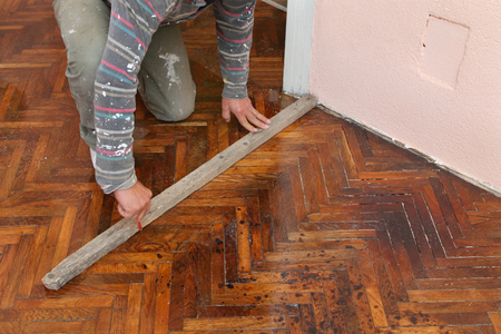 Worker  marking parquet floor with pencil before cutting photo