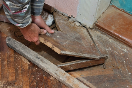 removing: Hand of worker removing old oak parquet