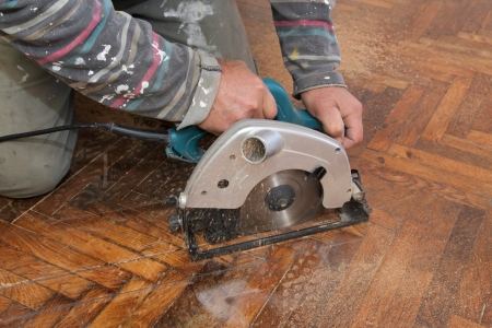 restoring: Worker cut old parquet floor with electric saw