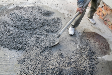 cement pile: Hand mixing concrete with worker and shovel