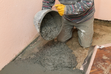 Home renovation, worker pouring concrete from pail photo