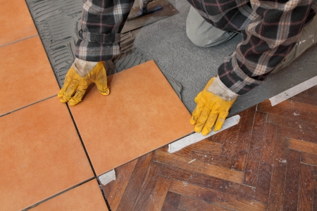 placing: Home renovation, worker placing tile to floor