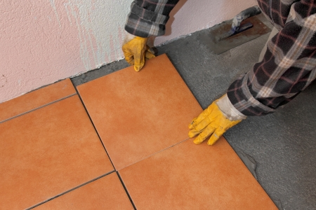 tile adhesive: Home renovation, worker placing tile to floor