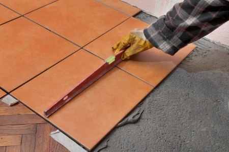 Home renovation, worker levelling tiles with level tool photo