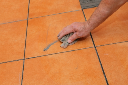 Home renovation, worker cleaning tile with rag photo