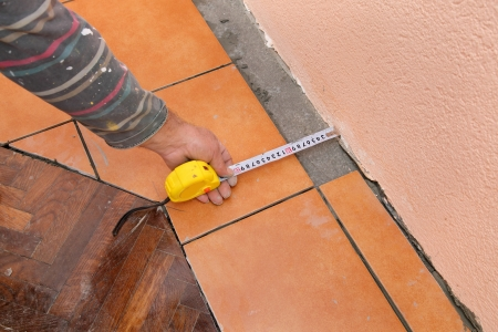 Worker measuring tile floor before tile cutting photo