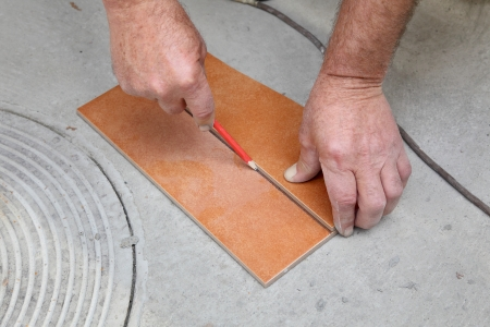 Worker measuring and marking tile for cutting photo