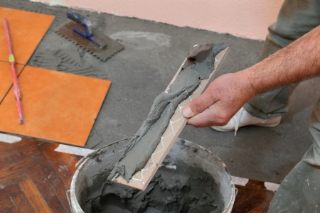 Home renovation, worker prepare tile with cement for placing photo