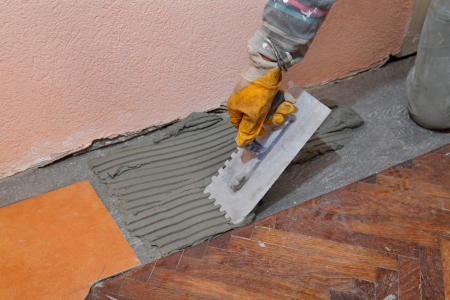 Home renovation, worker trowel spreading mortar for ceramic tile photo