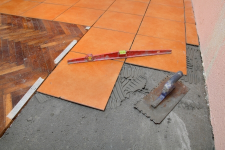 leveling: Home renovation tools, trowel and level at tiles, mortar