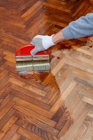 treated board: Varnishing of oak parquet floor, workers hand in glove and brush Stock Photo