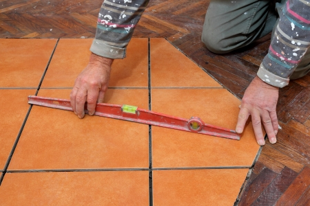 leveler: Home renovation, worker levelling tiles with level tool