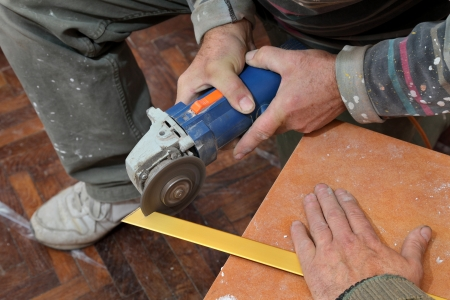 Home renovation, worker cut tile trim profiles with electric grinder photo