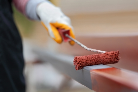 Worker painting  steel tube with paintroller selective focus
