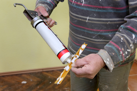 Plumber caulking silicone from cartridge to aluminum tile trim profile photo