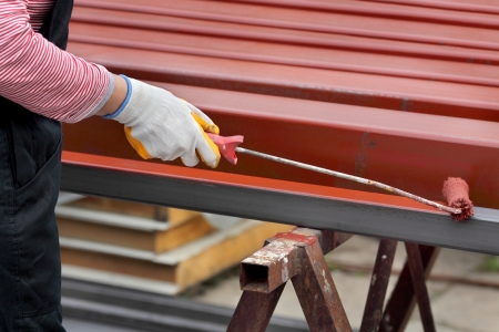 paintroller: Worker painting  steel tube with paintroller selective focus on hand