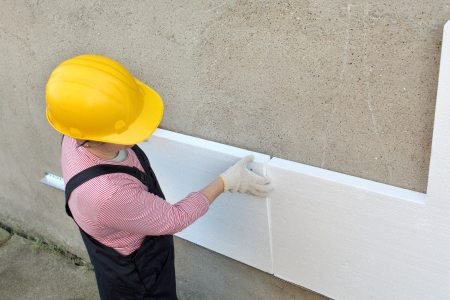 placing: Female worker placing styrofoam sheet insulation to the wall Stock Photo